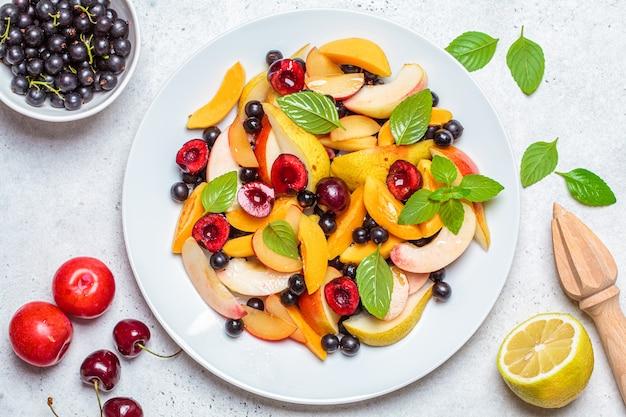 Macedonia di frutta con frutti di bosco in zolla bianca, sfondo bianco, vista dall'alto. concetto di cibo vegano sano. Foto Premium