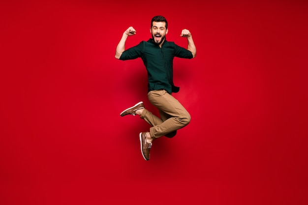 Il corpo pieno di allegro ragazzo salta mostra il suo potere mani muscolose tricipiti vincere concorso sportivo urlo sentire espressione pazza indossare scarpe da ginnastica camicia marrone verde Foto Premium