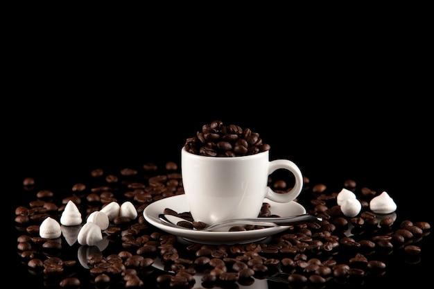 Tazza piena di chicchi di caffè su oscurità Foto Premium