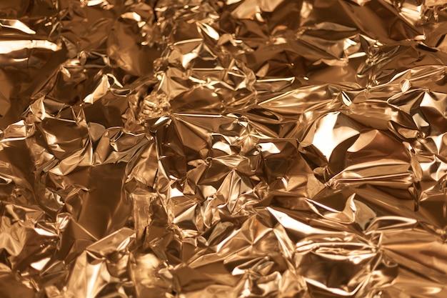 Presa da una cornice piena di fogli di alluminio dorati accartocciati Foto Premium