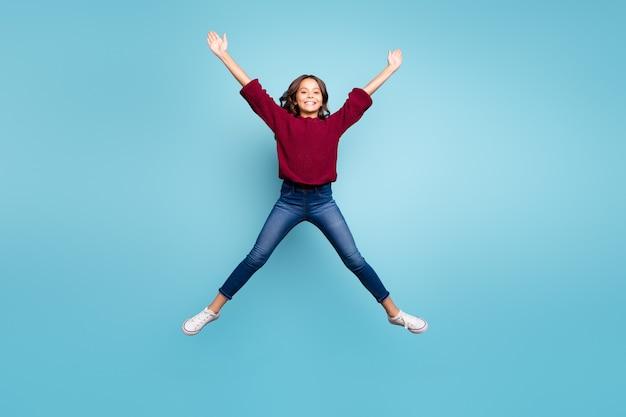 Foto a grandezza naturale del preteen positivo riccio allegro che modella la stella con le braccia delle gambe che saltano il fondo blu vivido isolato libero di colore Foto Premium