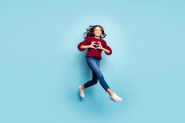Foto integrale di dimensioni del corpo dell'amica positiva allegra che salta in esecuzione che mostra il segno del cuore che indossa jeans denim maglione bordeaux isolato sfondo blu colore vivido Foto Premium