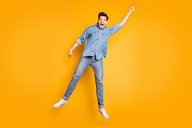 Foto a grandezza naturale di un uomo positivo urlante allegro in calzature bianche che volano via con l'ombrello dal vento che soffia isolato muro di colori vivaci Foto Premium