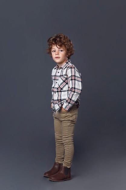 Integrale del ragazzino riccio sveglio in abbigliamento casual isolato su grigio Foto Premium