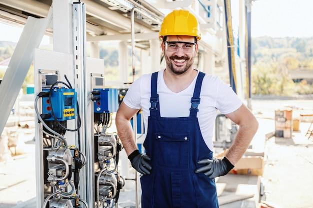 Integrale del lavoratore sorridente non rasato caucasico bello nel complesso e con il casco sulla testa che posa accanto al cruscotto in raffineria. Foto Premium