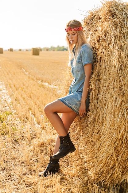 Immagine integrale della donna adorabile 20s che sta vicino al grande pagliaio nel campo dorato e sigaretta fumante durante la giornata di sole Foto Premium