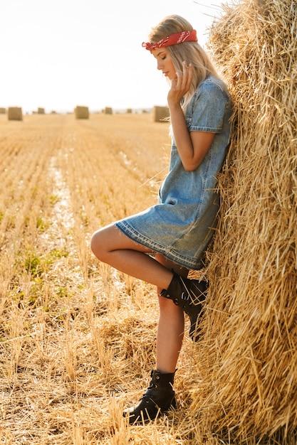 Immagine a figura intera della donna sessuale 20s in piedi vicino a un grande pagliaio in campo dorato e fumo di sigaretta durante la giornata di sole Foto Premium