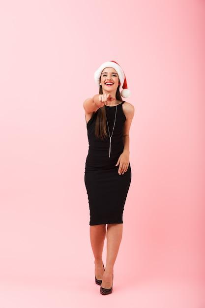 Ritratto integrale di una giovane donna allegra che indossa un abito che celebra il natale isolato su sfondo rosa, dito puntato Foto Premium