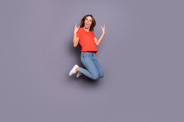 Per tutta la lunghezza della gioia allegra ragazza adolescente salta mostra il simbolo cornuto che indossa scarpe da ginnastica bianche in stile casual isolate su un muro di colore grigio Foto Premium
