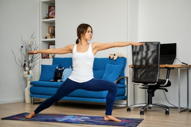 Vista laterale integrale della giovane donna che pratica yoga a casa, in piedi nella posizione del guerriero due Foto Premium