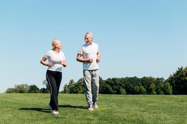 Anziani della foto a figura intera che corrono all'aperto Foto Premium