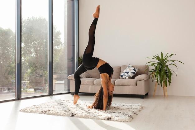 Donna piena del colpo che fa yoga a casa Foto Premium