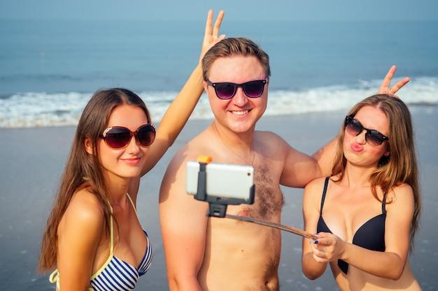 Amici divertenti fanno una foto su un autoadesivo sulla spiaggia Foto Premium