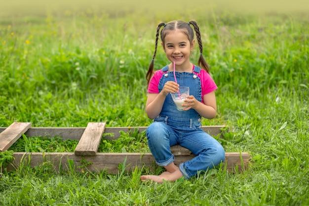 Divertente ragazza in tuta di jeans e una maglietta rosa, tiene un bicchiere di latte su un prato verde Foto Premium