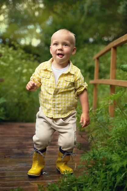 Ragazzino divertente in stivali di gomma gialli si trova sul ponte Foto Premium
