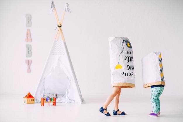 Bambini divertenti nella stanza luminosa con sacchi di carta sulle teste sul wigwam dei bambini Foto Premium