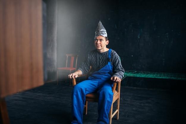 Uomo divertente in cappello di carta stagnola si siede sulla sedia, concetto di paranoia. ufo, teoria del complotto, protezione dal furto di cervello, fobia Foto Premium