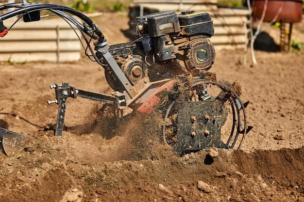 L'uomo del giardiniere coltiva il terreno a terra con il trattore o il motozappa, il cutivator, la miiling machine, preparano per piantare il raccolto in primavera. Foto Premium