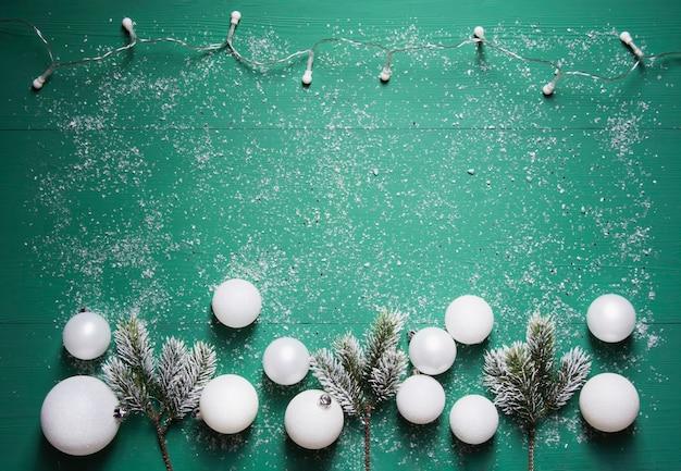 Una ghirlanda di rami di abete e palline di natale bianche si trovano su uno sfondo di legno verde Foto Premium