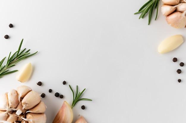 Guarnizione e ingredienti alimentari pepe nero rosmarino spicchi d'aglio e pezzi di aglio crudo Foto Premium