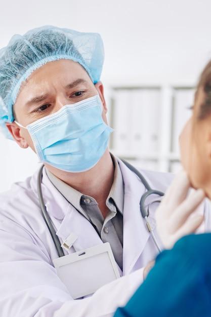 Medico di base che esamina le ghiandole del paziente Foto Premium
