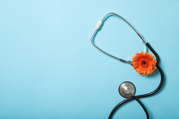 Gerbera e stetoscopio su una vista superiore colorata. Foto Premium