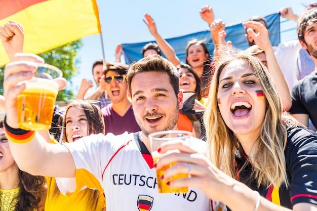 Sostenitori tedeschi che festeggiano allo stadio e bevono birra Foto Premium