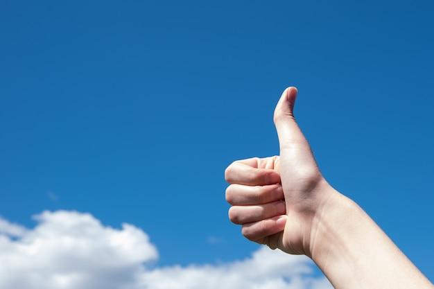 Gesto, pollice in alto su uno sfondo di cielo azzurro e nuvole, copia dello spazio Foto Premium