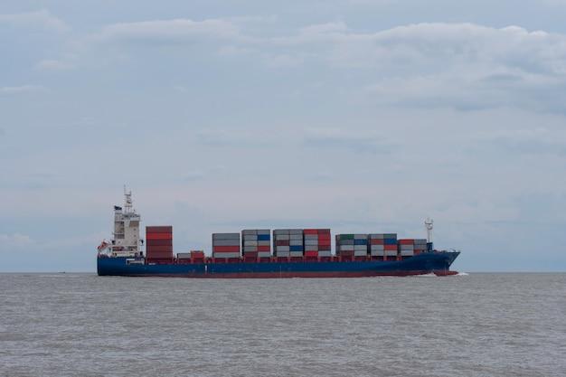 La nave gigante trasporta il contenitore di spedizione sul mare Foto Premium