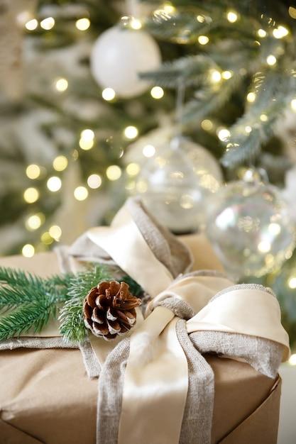 Regalo in scatola su sfondo di ghirlanda di natale e albero di capodanno Foto Premium