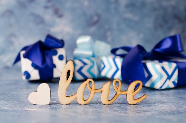 Il contenitore di regalo e l'iscrizione amano su fondo blu. concetto di regali per gli uomini. Foto Premium
