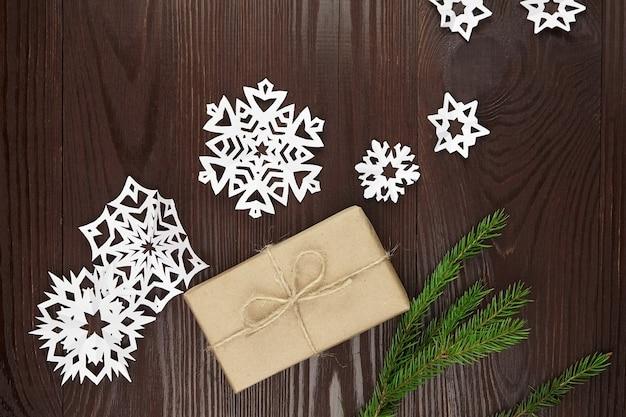 Confezione regalo con fiocchi di neve di carta e abete sulla tavola di legno Foto Premium