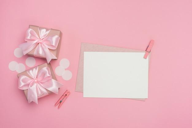 Contenitori di regalo con l'arco rosa del nastro e la cartolina d'auguri in bianco sulla tavola di rosa pastello. Foto Premium