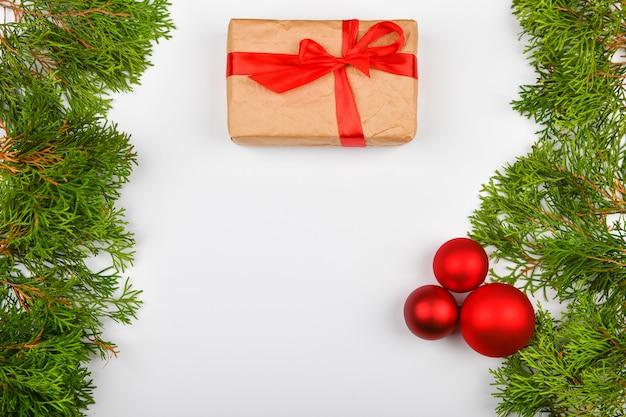 Confezione regalo con fiocco rosso su uno spazio bianco. conifere rami verdi su uno spazio bianco Foto Premium