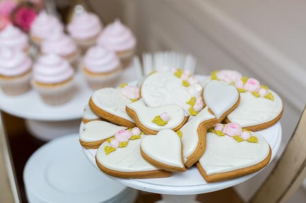 Biscotti di panpepato e biscotti sulla tavola festiva con i dolci. pasticcini alla moda come decorazione per le vacanze. bar dolce Foto Premium
