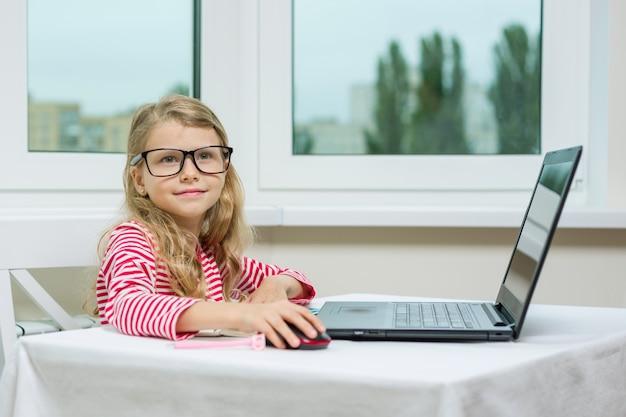 La ragazza in occhiali per adulti si siede al tavolo con il computer Foto Premium