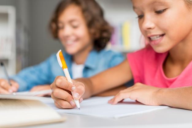 Ragazza e ragazzo che fanno i compiti insieme in biblioteca Foto Premium