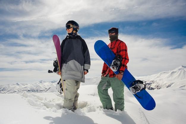 Ragazza e ragazzo che stanno nelle montagne con gli snowboard Foto Premium
