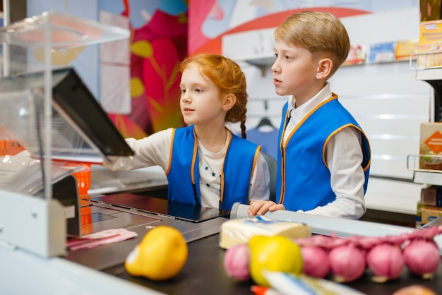 Ragazza e ragazzo in uniforme al registro che giocano a commessa Foto Premium