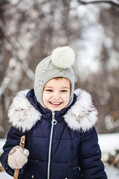 Bambina che cammina nella foresta invernale in una giacca blu e un cappello grigio Foto Premium