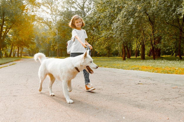 Bambina con un cane che cammina nel parco Foto Premium