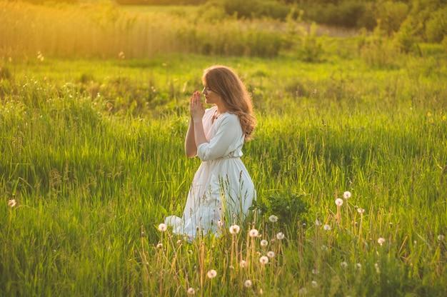 La ragazza chiuse gli occhi, pregando in un campo durante il bel tramonto Foto Premium