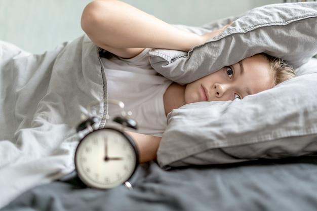 Ragazza che copre le sue orecchie di cuscino e sveglia Foto Premium