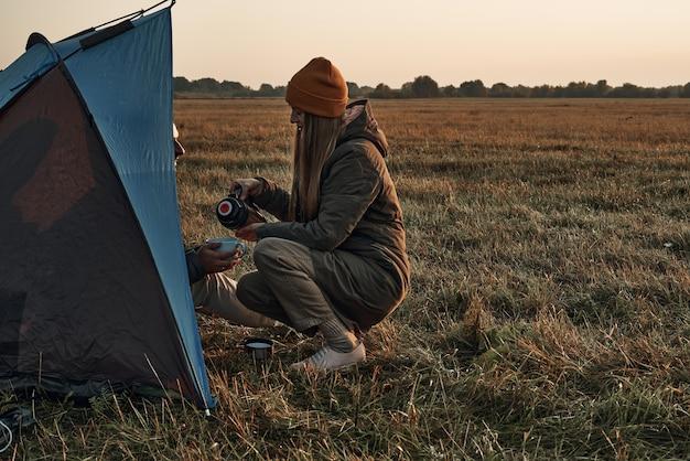 Una ragazza e un ragazzo in una tenda bevono da una tazza, periodo autunnale, viaggio. incontrano l'alba nella natura. Foto Premium