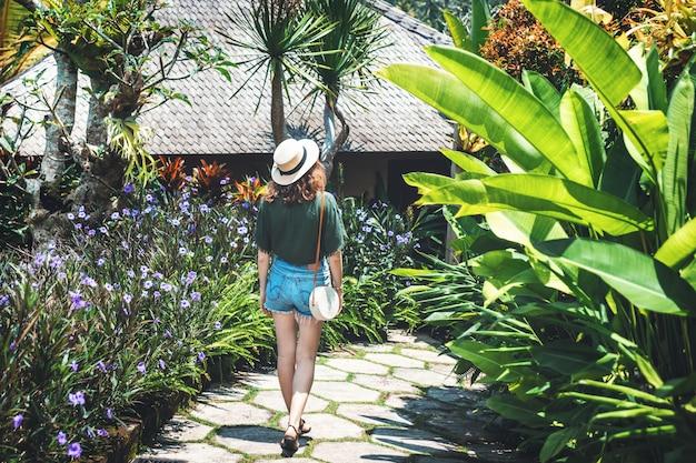 Una ragazza con un cappello cammina in una giornata di sole attraverso il territorio di un hotel di lusso a ubud. una giovane donna cammina lungo un sentiero circondato da fiori luminosi e piante tropicali, vista da dietro, bali, ubud. Foto Premium