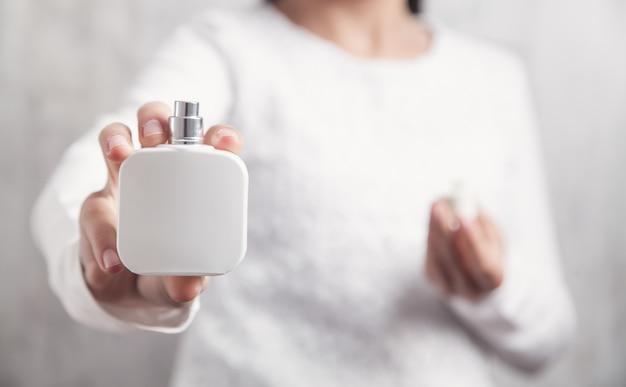 Bottiglia della holding della ragazza di profumo. Foto Premium