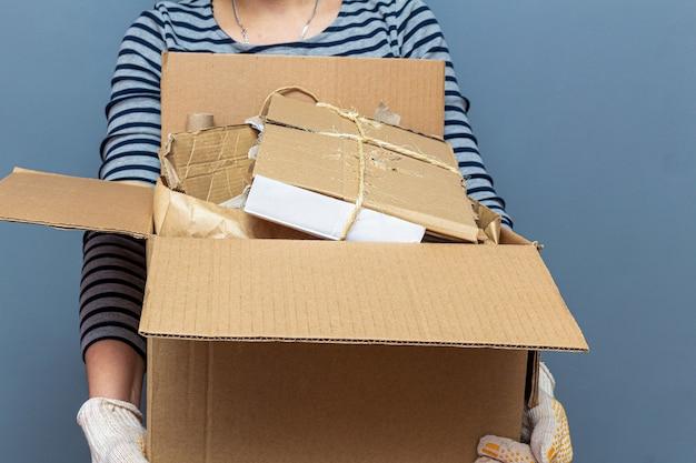 Ragazza con scatola di cartone con carta, cartone animato usato rifiuti, immondizia per il riciclaggio Foto Premium