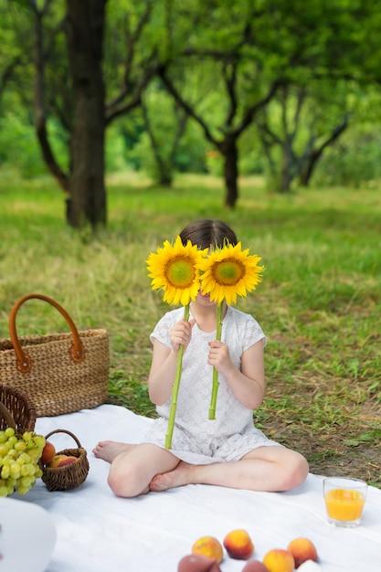 Girasole della tenuta della ragazza davanti al fronte all'aperto. festa all'aperto in giardino, picnic. Foto Premium