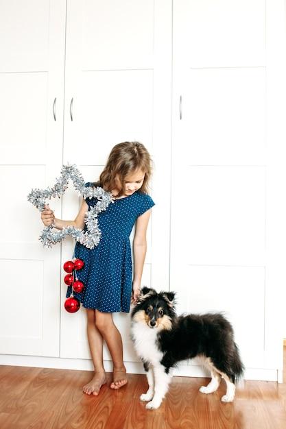 Una ragazza tiene una stella tra le mani per decorare la casa per il nuovo anno e natale, un cucciolo di cane che si prepara per le vacanze, aiuta i genitori, aspetta i regali Foto Premium