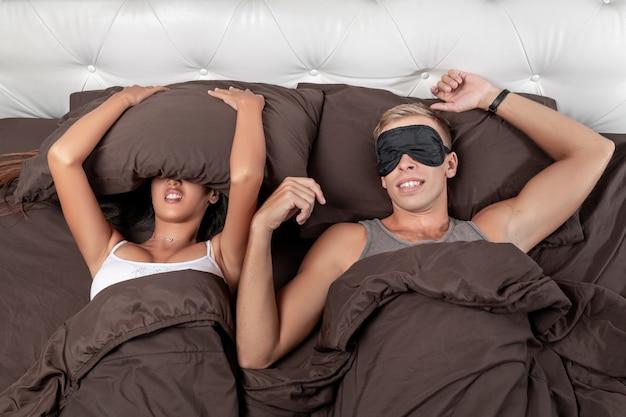La ragazza sta cercando di addormentarsi coprendosi la testa con un cuscino Foto Premium